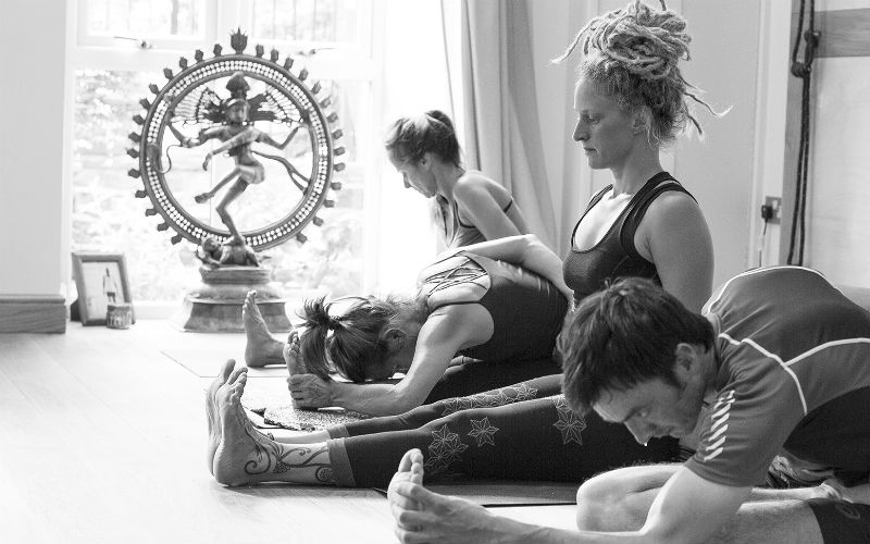 four people practising mysore style ashtanga yoga with shiva nataraja statue in background