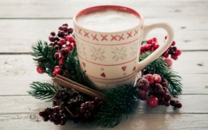 festive cup with hot drink and christmas wreath around it