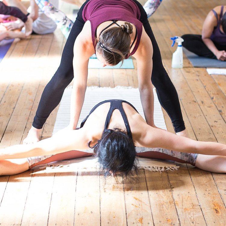 Rachel Woolhouse adjusting a student at Ashtanga Yoga Leeds