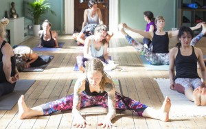 a group of people practising mysore style ashtanga with Joey Miles giving a physical adjustment